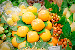 Stack ordered persimmon exhibited by a greengrocer Royalty Free Stock Photography