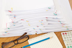 Stack of overload paper and reports on brown wood table. Stack of overload paper and reports have blue pencil on notebook with spectacles and calculator place on Stock Photography