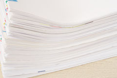 Stack of overload paperwork on wooden table. Stack of overload paperwork and reports place on wooden table Royalty Free Stock Image