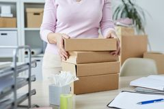 Stack of packed boxes with orders of online shop clients. And manager taking one of them royalty free stock image