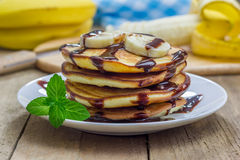 Stack of pancakes with banana and chocolate syrup Royalty Free Stock Images