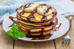 Stack of pancakes with banana and chocolate syrup Stock Images