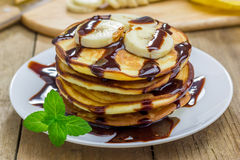 Stack of pancakes with banana and chocolate syrup Royalty Free Stock Photos
