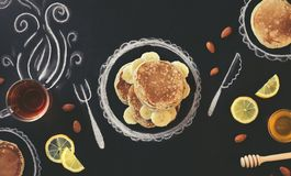 Stack of pancakes with banana, lemon and almond on chalk board with drawings Royalty Free Stock Images
