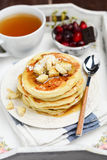 Stack of pancakes with banana, maple syrup, tea and cranberries Royalty Free Stock Photo