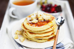 Stack of pancakes with banana, maple syrup, tea and cranberries Stock Photo