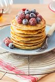 Stack of pancakes with berries and maple syrup. A stack of homemade pancakes topped with powdered sugar and a pile of chilled raspberries and blueberries. A royalty free stock photo