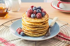 Stack of Pancakes with Berries and Maple Syrup. A stack of homemade pancakes topped with powdered sugar and a pile of chilled raspberries and blueberries. A mug stock photo
