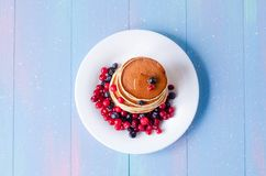 A stack of pancakes with berries on a white plate royalty free stock photography