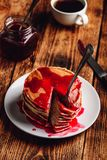 Stack of pancakes with berry jam. On white plate over wooden table stock images