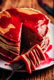 Stack of pancakes with berry jam. On white plate over wooden table stock photos