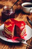 Stack of pancakes with berry jam. On white plate over wooden table stock photo