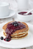 Stack of pancakes with black currant jam on a plate Stock Images