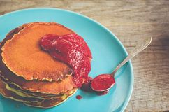 Stack of pancakes on a blue plate with red jam Royalty Free Stock Photo