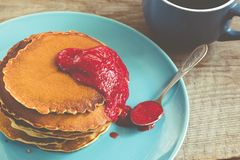 Stack of pancakes on a blue plate with red jam Royalty Free Stock Photography