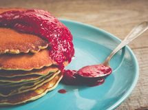 Stack of pancakes on a blue plate with red jam Royalty Free Stock Photos
