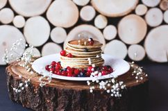 A stack of pancakes with blueberries and cranberries on a white plate stock images