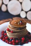 A stack of pancakes with blueberries and cranberries on a white plate stock photography