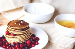 A stack of pancakes with blueberries and cranberries on a white plate stock photo