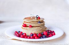 A stack of pancakes with blueberries and cranberries on a white plate. stock photos