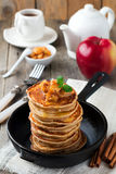 Stack of pancakes from buckwheat flour with baked apples and cinnamon on old wooden background. A healthy breakfast. Stock Image