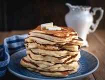 Stack of pancakes with butteron wooden background stock photos