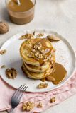 Stack of pancakes with caramel and walnuts on white plate stock photo