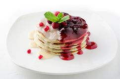 A stack of pancakes with condensed milk and berry jam. royalty free stock photography