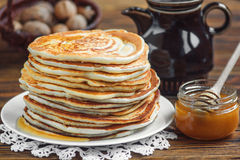 Stack of pancakes. Stack of delicious, homemade pancakes with honey on white plate on wooden background. Healthy breakfast, close up Stock Photos