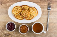 Stack of pancakes in dish, fork, bowls with jam, tea Stock Photography