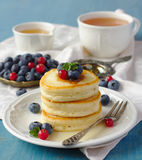 Stack of pancakes with fresh berries and honey Royalty Free Stock Images
