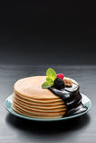 Stack of pancakes. With fresh raspberries and blackberries, in the melted chocolate and walnuts. Healthy breakfast concept. Space for text on the background Royalty Free Stock Images