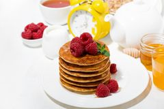Stack of pancakes with fresh raspberries for breakfast. On white table, horizontal Stock Photos