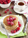 Stack of pancakes with fresh raspberries. Stack of pancakes with fresh raspberries and cup of tea Stock Photos