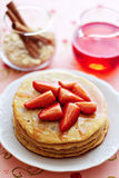 A stack of pancakes with fresh strawberries and sy Stock Photos