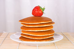 Stack of pancakes with a fresh strawberry on top Royalty Free Stock Photos