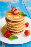 Stack of pancakes fritters with strawberries and honey on a pl royalty free stock image