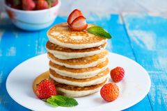Stack of pancakes fritters with strawberries and honey on a pl Stock Images