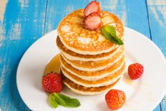 Stack of pancakes fritters with strawberries and honey on a pl stock photo
