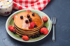 Stack of pancakes with frozen berries and honey on black background. Selective focus. Royalty Free Stock Photography