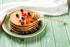Stack of pancakes with frozen berries and honey on wooden table. Selective focus Stock Image