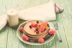 Stack of pancakes with frozen berries poured with honey on wooden kitchen table. Selective focus. Toned. Stock Photography