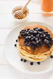 Stack of pancakes with frozen blueberries and honey Stock Images