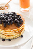 Stack of pancakes with frozen blueberries and honey Stock Photo