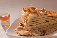 Stack of pancakes with fruits, nuts and honey. Stock Images