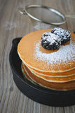 Stack of pancakes in frying pan with blackberries and maple syru Stock Image