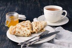 A stack of pancakes with honey for Maslenitsa. A stack of pancakes with sour cream and honey for Maslenitsa royalty free stock photography