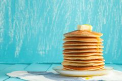 Stack of pancake with honey and butter on top. Stack of pancakes with honey and piece of butter on plate which stands on napkin on blue wooden table. Copyspace Stock Image