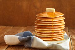 Stack of pancake with honey and butter on top. Stack of pancakes with honey and piece of butter on plate which stands on napkin on wooden table. Copyspace Royalty Free Stock Photo