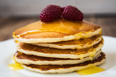 Stack of pancakes with honey and raspberry on white plate Stock Images